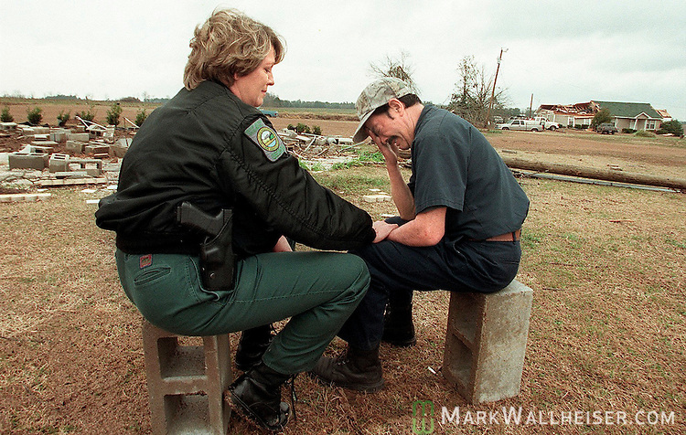 "Georgia Department of Natural Resourses Ranger Sue Furney (L) comforts Jaime Chong-Chaparro after an early morning tornado ripped through the Pine Level Community north of Cairo on Valentines Day killing his fiance who lived in the trailer that used to be located on the cinder blocks at left.  Furney came by and spotted Chong-Chaparro sitting on one of the cinderblocks from the completely destroyed trailer alone and stopped to listen to him tell of his love for his fiance.  ""She will be in my heart forever"", said Chong-Chaparro, adding, ""she is with the angles."""