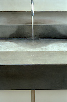 A detail of the bathroom illustrating the pared-down design of the concrete wash basin and single stainless-steel tap