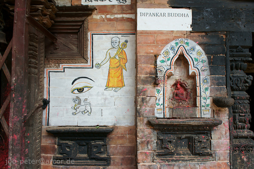 wall in courtyard of a traditional brick-stone house in Bhaktapur, Nepal with typical Newar culture mixture of Buddhist and Hinduist symbols, a monk in saffron clothes, a shrine with Buddha relief with signs of worshipping (red pigment)typical for Hindu culture. Wooden parts of architecture are carved with ornaments.