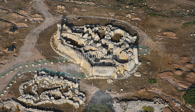 Aerial view of the Hagar Qim Temple complex, Malta, pictured on June 5, 2008, in the morning. The Republic of Malta consists of seven islands in the Mediterranean Sea of which Malta, Gozo and Comino have been inhabited since c.5,200 BC. It has been ruled by Phoenicians (Malat is Punic for safe haven), Greeks, Romans, Fatimids, Sicilians, Knights of St John, French and the British, from whom it became independent in 1964. Nine of Malta's important historical monuments are UNESCO World Heritage Sites, including  the temple of Hagar Qim which stands on a hilltop in the south of the island of Malta. Typical to Maltese megalithic temple design, it  has a trilithon entrance, outer bench and orthostats. A wide forecourt with a retaining wall and a passage runs through the middle of the building. Although the main temple dates to 3600-3200 BC, the northern ruins are considerably older. The site was excavated during the 19th and 20th centuries. Picture by Manuel Cohen.