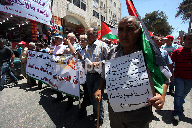 Palestinian protesters demonstrating against the upcoming negotiations between Palestinian leaders and Israel, march towards headquarters of Palestinian president Mahmud Abbas, in the West Bank city of Ramallah on July 28, 2013. Israeli Prime Minister Benjamin Netanyahu was seeking cabinet approval for a contentious release of 104 veteran Palestinian and Israeli-Arab prisoners, to coincide with the resumption of peace talks which have been stalled since September 2010. Photo by Issam Rimawi