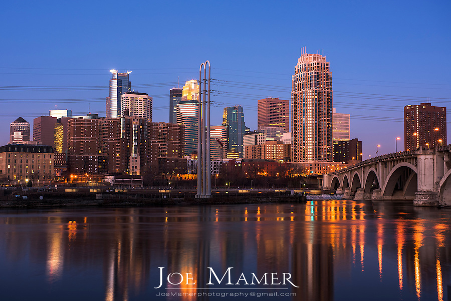 Minneapolis skyline at dawn with the Mississippi River in the foreground.