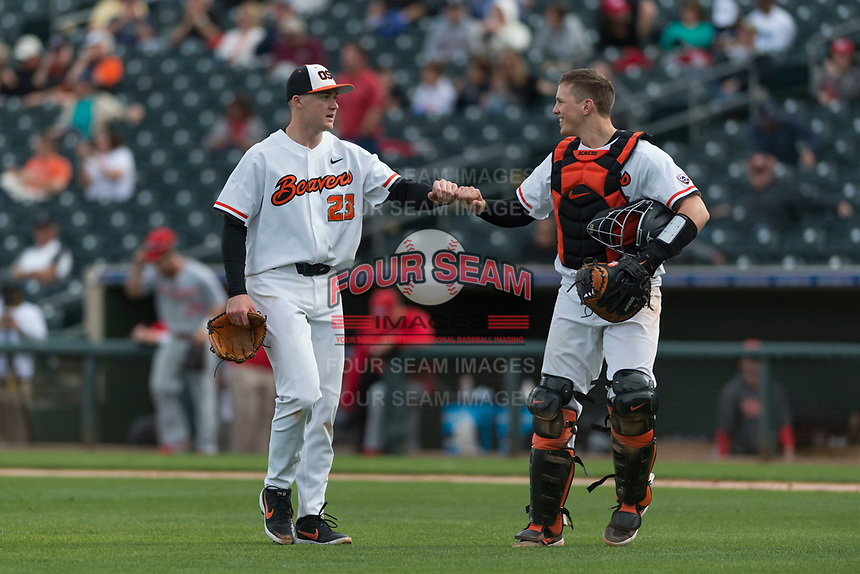 Oregon State Beavers catcher Adley Rutschman (35) fist bumps Kevin Abel (23) between innings of a game against the New Mexico Lobos on February 15, 2019 at Surprise Stadium in Surprise, Arizona. Oregon State defeated New Mexico 6-5. (Zachary Lucy/Four Seam Images via AP)