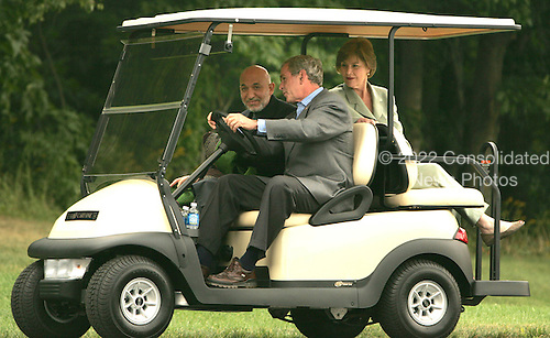Camp David, MD - August 5, 2007 -- United States President George W. Bush gives President Hamid Karzai of Afghanistan a ride as first lady Laura Bush looks on from the  backseat of a VIP golfcart at Camp David, Maryland on Sunday, August 5, 2007.  .Credit: Dennis Brack - Pool via CNP