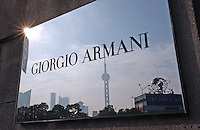 The Pudong area of shanghai is reflected in a Giorgio Armani  sign outside the flag-ship store on the Bund in Shanghai,China. .