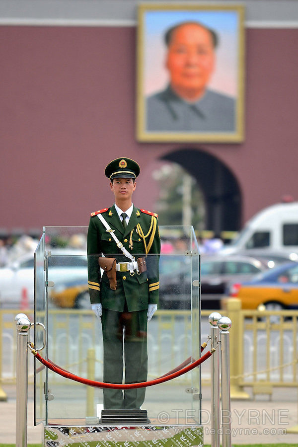 Guard standing at attention in Tiananmen Square with large portrait of Mao in background.