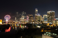 New Years Fireworks display explode over Austin, Texas skyline and beautiful calm Lady Bird Lake.