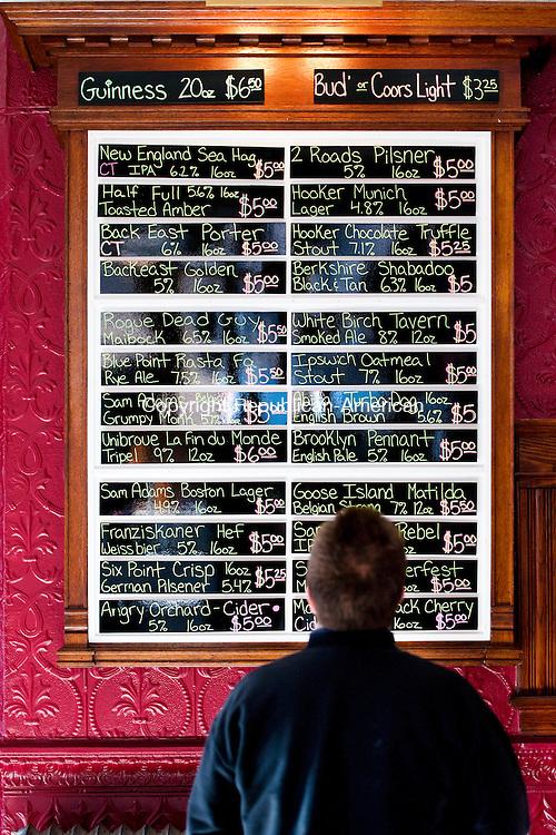 NAUGATUCK, CT - 9 January 2014-010914EC05--    Customer Mark Szamatulski checks out the craft beer menu offered by The Corner Tavern in Naugatuck. Erin Covey Republican-American.