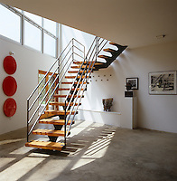 Contemporary artwork covers the walls of this concrete-floored entrance hall and the skeletal staircase leads up to the main living area