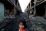 A girl in the Smokey Mountain neighborhood of Manila. The area is named for a now-closed garbage dump that dominates the area.