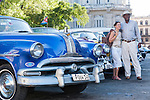 Havana, Cuba; a female tourist poses for a picture with the owner of a classic blue 1953 Pontiac convertible parked next to a yellow and a purple 1954 Chevys on the street in Old Havana
