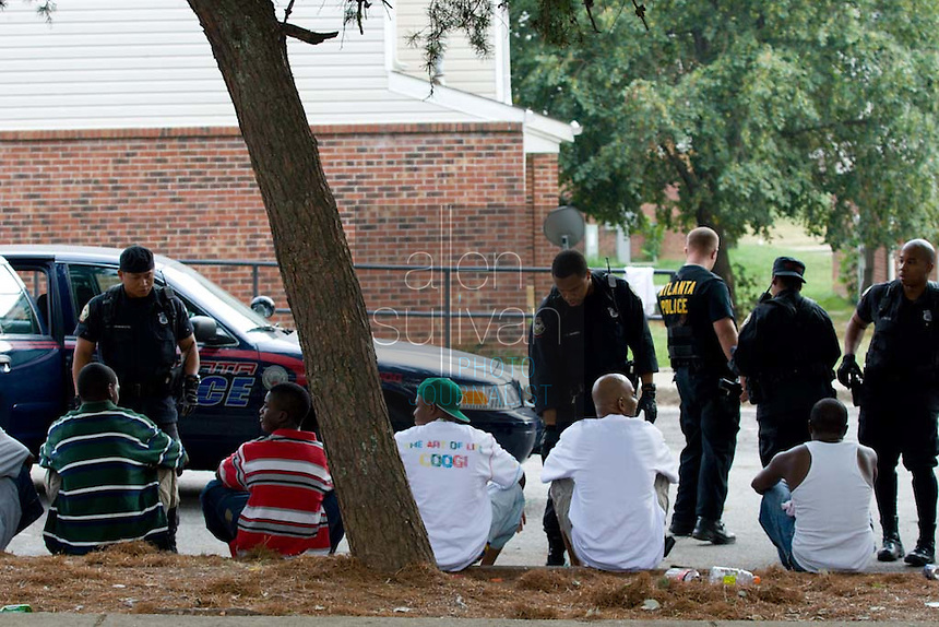 Atlanta Police Department officers speak to people detained during sweeps in the Vine City Terrace Apartments on Saturday, August 18, 2007. Police said they found drugs, drug money and at least one stolen car during the sweeps, which also included Bowen Homes.