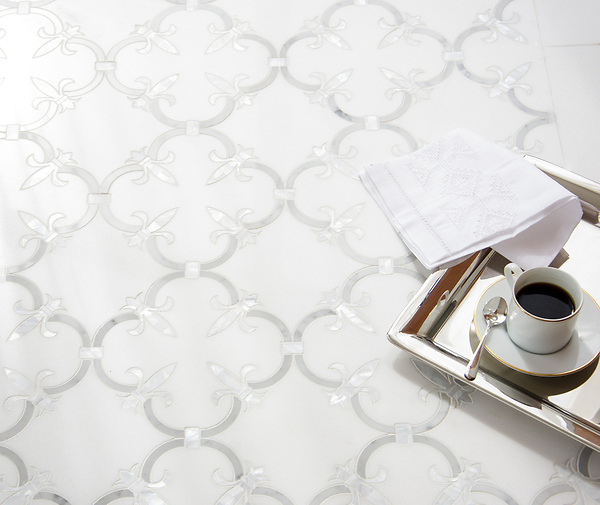 Fleur de Lys, a waterjet stone mosaic, shown in polished Thassos, polished Carrara, and Shell, is part of the Jardins Français™ collection by Caroline Beaupere for New Ravenna.