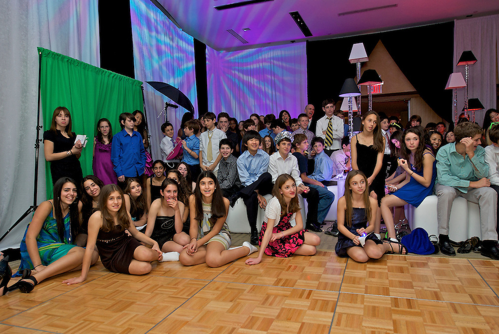 Kids gathered around the dance floor watching the video montage at a Mitzvah party.