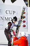 Canadian Nathan Smith accepts flowers for his first place finish at The International Biathlon Union Cup # 7 Men's 10 KM Sprint held at the Canmore Nordic Center in Canmore Alberta, Canada, on Feb 16, 2012. This was Nathan's third win of three sprints held in Canmore.  Two sprints were held the previous weekend in Cup 6, and this one for cup 7.  Photo by Gus Curtis.