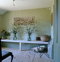 The pale green entrance hall has a pebble mosaic inlaid into the stone floor and oversized vases filled with cow parsley