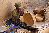 Farmer repairing calabash with fibres of  Burassus aethiopum mart
