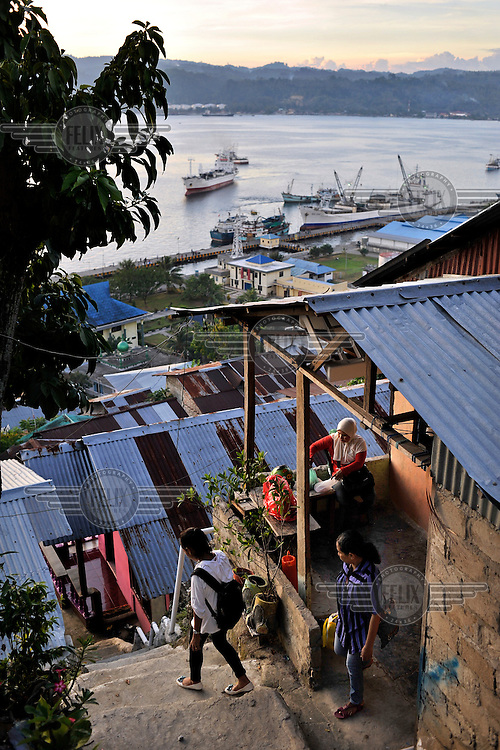 The ramshackle settlements on the outskirts of Ambon City - a mainly Muslim area within the Christian southern sector of Ambon Island - overlooking the main port, at dusk. The 1999-2002 religious war between Maluku's Christian and Muslim populations, mainly centred on Ambon Island, led to over 5000 deaths and to around 500,000 people become displaced. Destroyed homes and offices, churches and mosques are slowly being either torn-down or renovated.  Urban centres, such as Ambon City, continue to be split along largely sectarian lines, and tensions are never far below the surface. Riots between Christian and Muslim youths erupted in September 2011 and, most recently, June 2012, though luckily simmered down just as quickly, partly due to community leaders learning how to defuse tensions from the earlier, more devastating, conflagration. /Felix Features