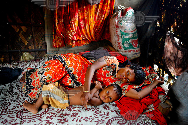 A woman and her son lie on a bed in their home in one of the city's slum districts. It is thought that more than six million people live in slums in Dhaka.