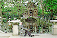 An elderly gentleman enjoying a beautiful spring day, while seated beside a fountain within the Luxembourg Gardens, Paris France
