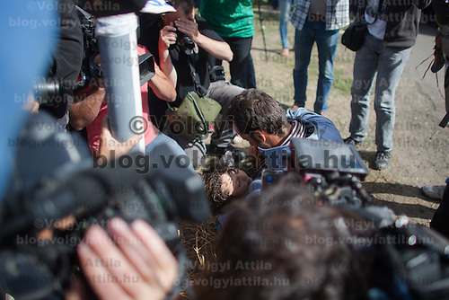 Reporters record as illegal migrant carries his unconscious son because of fatigue and heat stroke near Roszke (about 174 km South of capital city Budapest), Hungary on September 07, 2015. ATTILA VOLGYI