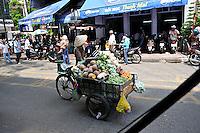 A street vendor selling vegetables on a busy city street. Ho Chi Minh City (Saigon), Vietnam