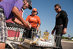 Rueben Lopez, left, and Sergio Macias, right, load food into their cart with the help of volunteer Elida DSilva, center, at a food distribution center in Crystal City, Texas. The San Antonio Food Bank makes monthly deliveries to Crystal City in Zavala County, Texas, which has the nation's highest rate of food insecurity. October 2, 2012. Copyright Lance Rosenfield / Prime