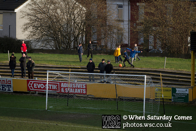 Prescot Cables 2 Brighouse Town 1, 13/02/2016. Hope Street, Northern Premier League. Boys playing football behind the goal during the first-half as Prescot Cables take on Brighouse Town in a Northern Premier League division one north fixture at Valerie Park. Founded in 1884, the 'Cables' in their name came from the largest local employer, British Insulated Cables and they have played in their current ground, also known as Hope Street, since 1906. Prescott won the match 2-1 watched by a crowd of 189. Photo by Colin McPherson.