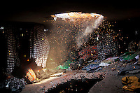 Sparks fly as a Bangladeshi rescuer works at the site of a building that collapsed Wednesday in Savar, near Dhaka, Bangladesh, Friday, April 26, 2013.