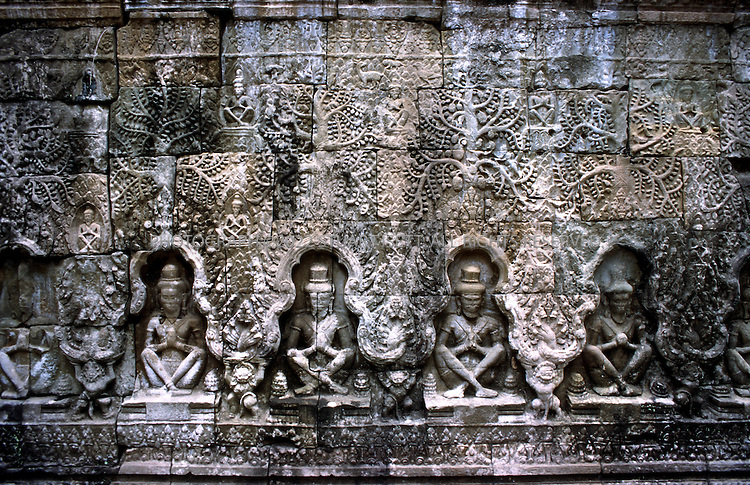 4/20/2003--Angkor Wat Temples, Siem Reap, Cambodia ..TA PHROM.  .Ta Prohm is locating southwest of the East Mebon and east of Angkor Thom. Its outer enclosure is near the corner of Banteay Kdei. It was built about mid-12th century to early 13th century (1186) by the King Jayavarman VII, dedicated to the mother of the king (Buddhist) replica to Bayon style of art. ..BACKGROUND ..Ta Prohm is the undisputed capital of the kingdom of the Trees. It has been left untouched by archaeologists except for the clearing of a path for visitors and structural strengthening to stave of further deterioration. Because of its natural state, it is possible to experience at this temple the wonder of the early explorers when they came upon these monuments in the middle of the nineteenth century. .Shrouded in dense jungle the temple of Ta Prohm is ethereal in aspect and conjures up a romantic aura. Fig, banyan and kapok trees spread their gigantic roots over stones, probing walls and terraces apart, as their branches and leaves intertwine to form a roof over the structures. Trunks of trees twist amongst stone pillars. The strange, haunted charm of the place entwines itself about you as you go, as inescapably as the roots have wound themselves about the walls and towers', wrote a visitor 40 years ago. ..A Sanskrit inscription on stone, still in place, give details of the temple. Ta Prohm 3,140 villages. It took 79,365 people to maintain the temple including 18 great priests, 2,740 officials, 2,202 assistants and 615 dancers. Among the property belonging to the temple was a set of golden dishes weighing more than 500 kilograms, 35 diamonds, 40,620 pearls, 4,540 precious stones, 876 veils from China, 512 silk beds and 523 parasols. Even considering that these numbers were probably exaggerated to glorify the king, Ta Prohm must have been an important and impressive monument. ..All photographs ©2003 Stuart Isett.All rights reserved.This image may not be reproduced without expressed written