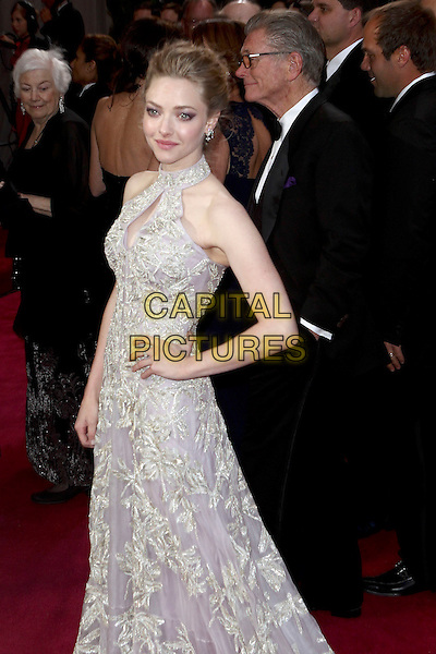 Amanda Seyfried (wearing Alexander McQueen).85th Annual Academy Awards held at the Dolby Theatre at Hollywood & Highland Center, Hollywood, California, USA..February 24th, 2013.oscars half 3/4  length dress hand on hip embellished high collar keyhole bust cut out lilac purple sheer gold embroidered print sleeveless .CAP/ADM/SLP/COL.©Colin/StarlitePics/AdMedia/Capital Pictures