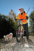 Woman hunter on her bicycle with her dog