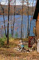 Man age 55 taking a wood chopping break at cabin on Sand Lake.  Cumberland  Wisconsin USA