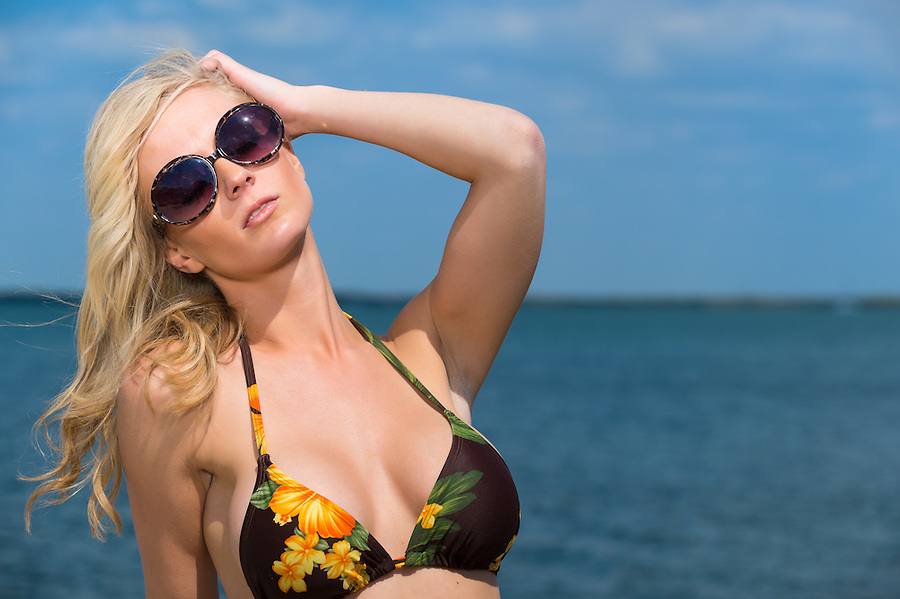 Beautiful young blond woman in sunglasses and bikini posing with her head tilted and hand to her forehead against a tropical ocean backdrop