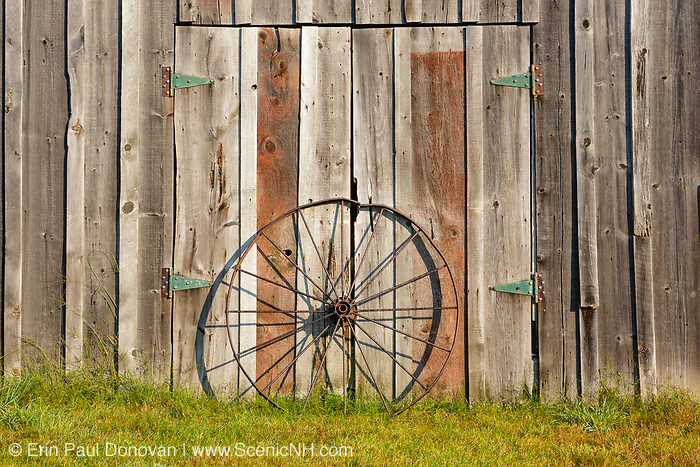 Wagon wheel keeps the doors of a barn closed at the Morrison House Museum in Londonderry, New Hampshire  USA which is part of scenic New England
