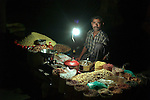 Street vendor working under calor gas light in New Delhi, India.