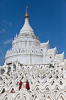 Myanmar, Burma.  Mingun, near Mandalay.  Two Young Novice Buddhist Monks Standing on Hsinbyume Paya Stupa, completed 1816.  Seven wavy terraces around the stupa represent the seven mountain ranges around Mt. Meru, center of the universe in Hindu and Buddhist cosmology.