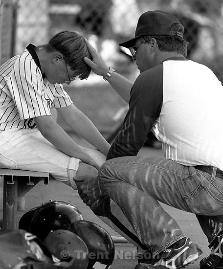 Coach comforts his son after a collision at home plate.<br />