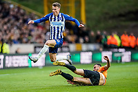 7th March 2020; Molineux Stadium, Wolverhampton, West Midlands, England; English Premier League, Wolverhampton Wanderers versus Brighton and Hove Albion;  Romain Saïss of Wolverhampton Wanderers clears the ball as Solly March of Brighton & Hove Albion hurdles the challenge