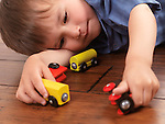 Two year old boy playing with a colorful wooden toy train on hardwood floor