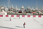 Three people skate on the ice rink in Monaco with large yachts docked in the background.