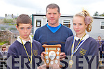 AWARD: Gerry Horgan of the Farranfore-Maine Valley Athletic Club presenting the perpetual shield from the recent juvenile athletics to Joe Hoare and Chloe Barrett of Brackloon national school, the overall winners at the event.