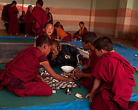A moment in the day of student Buddhist monks at a monastery in the Himalayan foothills of Sikkim, India. Playing board games.