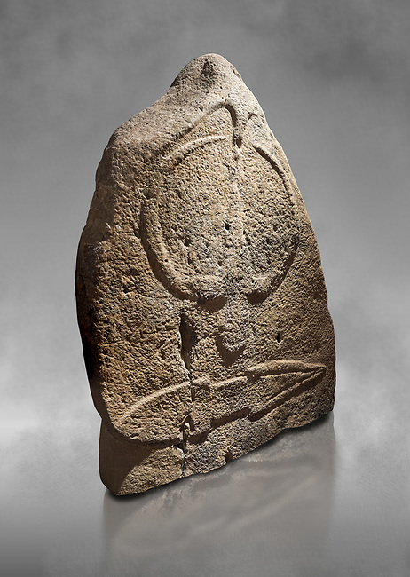 Late European Neolithic prehistoric Menhir standing stone with carvings on its face side. The representation of a stylalised male figure starts at the top with a long nose from which 2 eyebrows arch around the top of the stone. below this is a carving of a falling figure with head at the bottom and 2 curved arms encircling a body above. at the bottom is a carving of a dagger running horizontally across the menhir. Excavated from Barilli I site,  Laconi. Menhir Museum, Museo della Statuaria Prehistorica in Sardegna, Museum of Prehoistoric Sardinian Statues, Palazzo Aymerich, Laconi, Sardinia, Italy