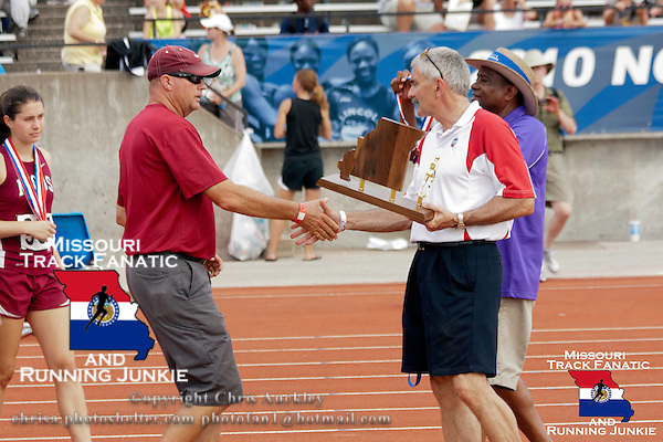 MICDS Head Track and Field Coach Jim Lohr gets a handshake from MICDS Athletic Director and MSHSAA St. Louis District Board of Directors member Don Maurer before accepting the Class 3 Girls 4th place team trophy at the Missouri High School Class 3-4 State Track and Field Championships in Jefferson City, Saturday, May 26. MSHSAA Board of Directors member and St. Louis Public Schools Athletic Director Travis Brown prepares to give the team medal to Coach Lohr.