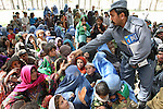An Afghan police officer hands out snacks to women as they wait to be admitted into the district center of  Shar-e-Safa in Zabul province, Afghanistan. U.S. troops provided medical care, and Afghan police distributed winter clothes, food staples and other relief items to about 200 people before they ran out of supplies.  Aug. 25, 2008. DREW BROWN/STARS AND STRIPES