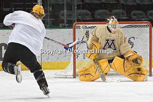 Kellen Briggs makes a save on Blake Wheeler - The University of Minnesota Golden Gophers took part in their morning skate at Ralph Engelstad Arena in Grand Forks, North Dakota, on Saturday, December 10, 2005.