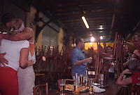 Couple in love and group of friends have drink ( chope - draught beer ) and eat at pizza at Amarelinho bar and restaurant in Cinelandia, a bohemian area in downtown Rio de Janeiro - chairs upside down indicating waiters want to close the doors but clients insist on remain enjoying nightlife.