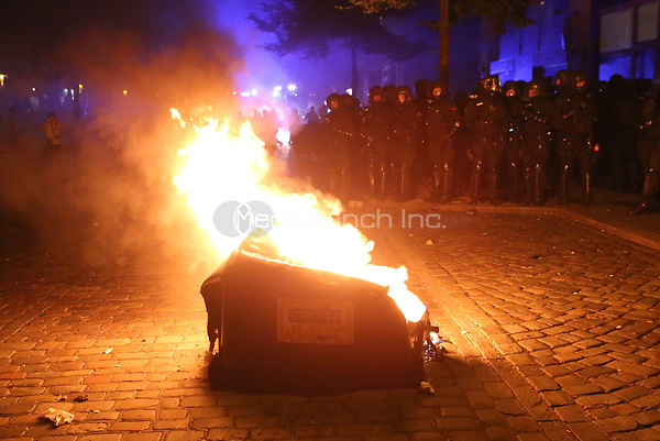 Police in riot gear stand in front of a burning bin during demonstrations against the G20 summit in Hamburg, Germany, 6 July 2017. The summit, a meeting of the governments of the twenty largest world economies, begins on the 7 July and concludes on the 8 July. Photo: Bodo Marks/dpa /MediaPunch ***FOR USA ONLY***