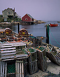 Halifax County, Nova Scota<br /> Wood lobster traps a dock in Peggy's Cove with morning fog enveloping the village and harbor